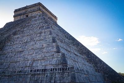 gray brick wall under blue sky during daytime mayan pyramid teams background