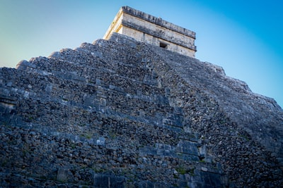 gray and black concrete building under blue sky during daytime mayan pyramid teams background