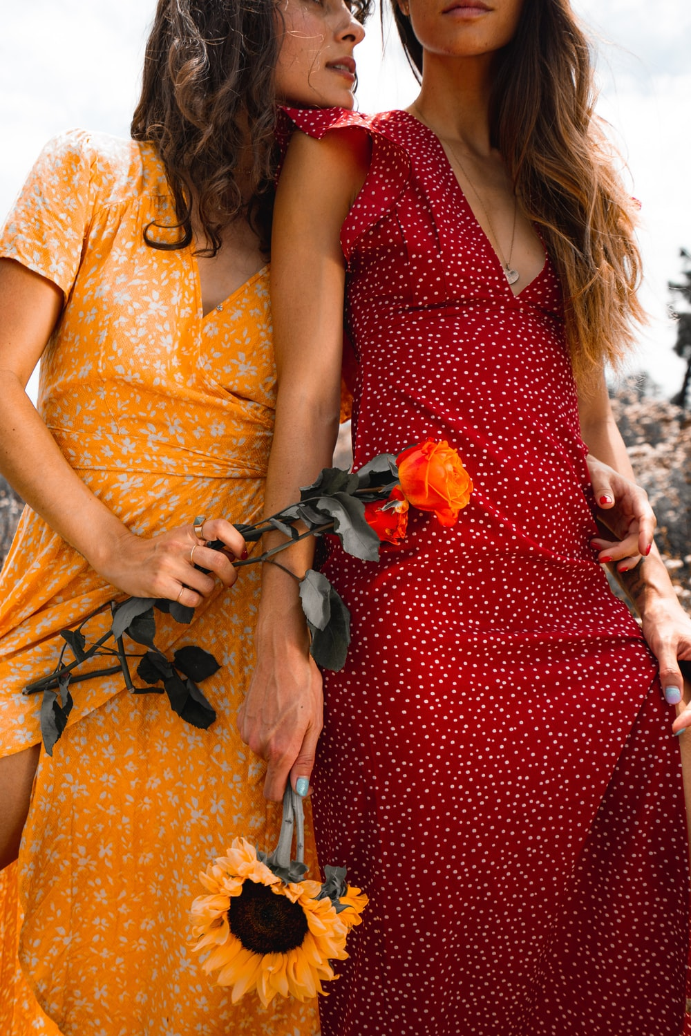 woman in yellow and red floral dress holding orange flower