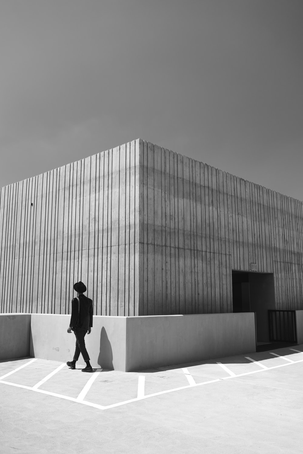 grayscale photo of man in black jacket and pants standing beside building
