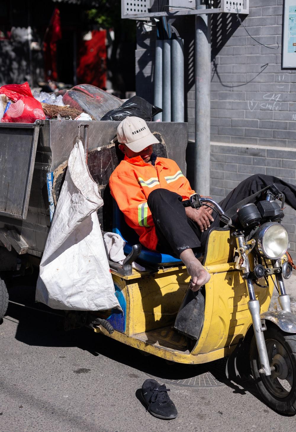 man in orange and white jacket sitting on yellow motorcycle during daytime