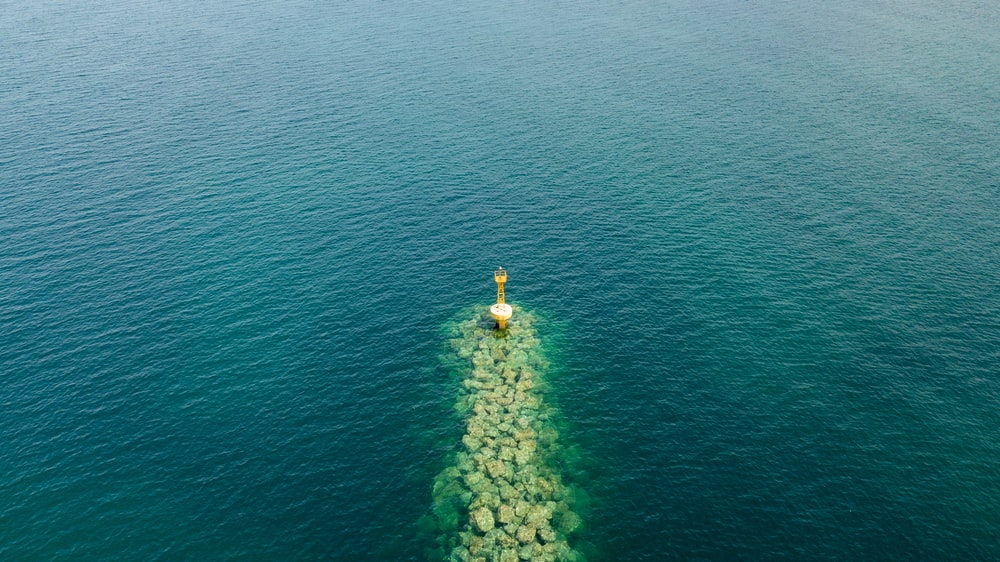 person in yellow jacket and yellow pants standing on rock in the middle of the sea