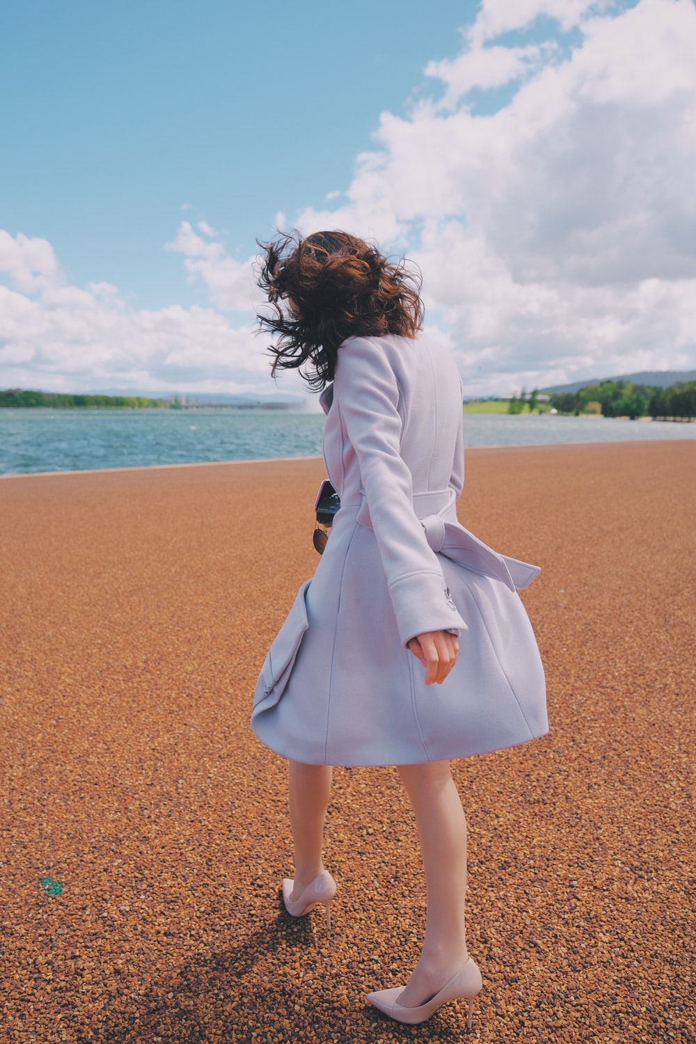woman in white long sleeve dress standing on brown sand near body of water during daytime