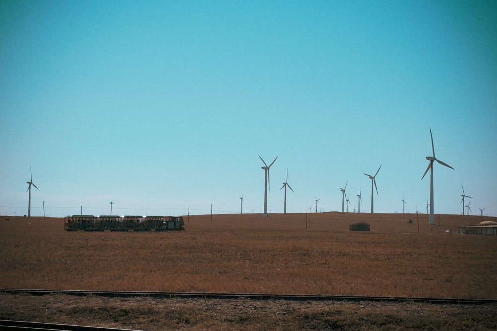 wind turbines on brown field under blue sky during daytime