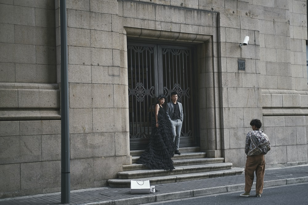 man and woman standing in front of black metal gate