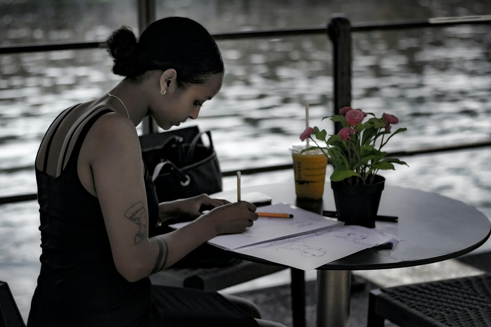 woman in black tank top writing on white paper