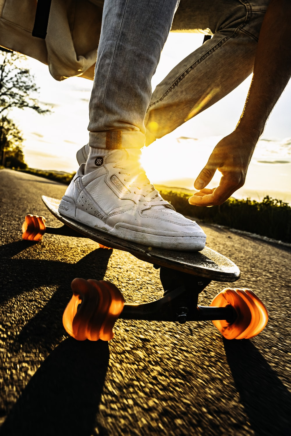 person in white pants and white shoes riding skateboard during daytime