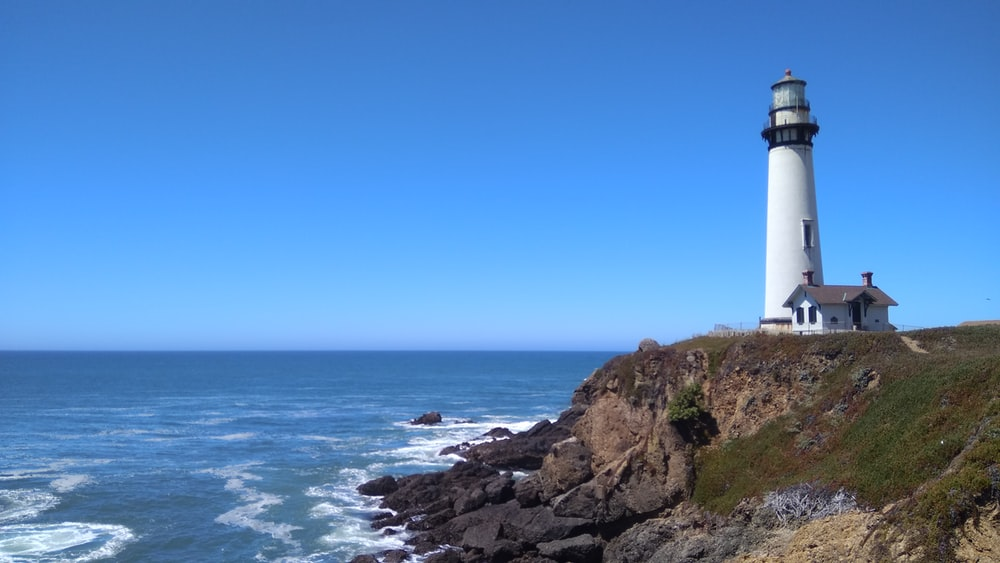white lighthouse on brown rocky shore during daytime