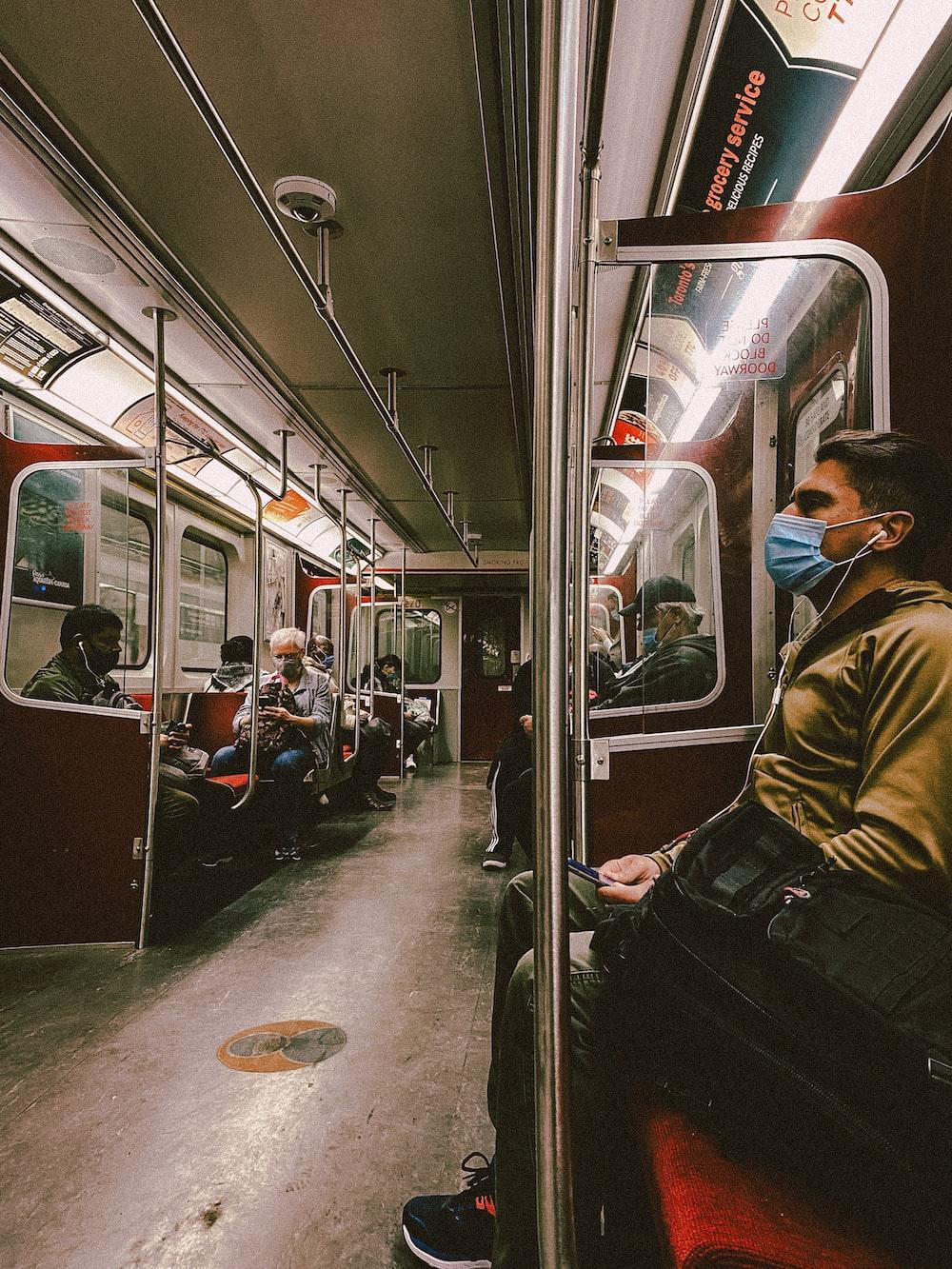 man in brown jacket sitting on train seat