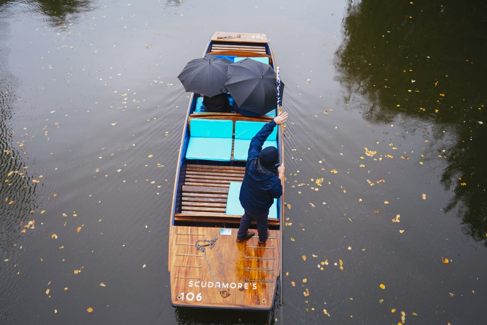 man in blue shirt and blue denim jeans sitting on brown wooden boat on water during