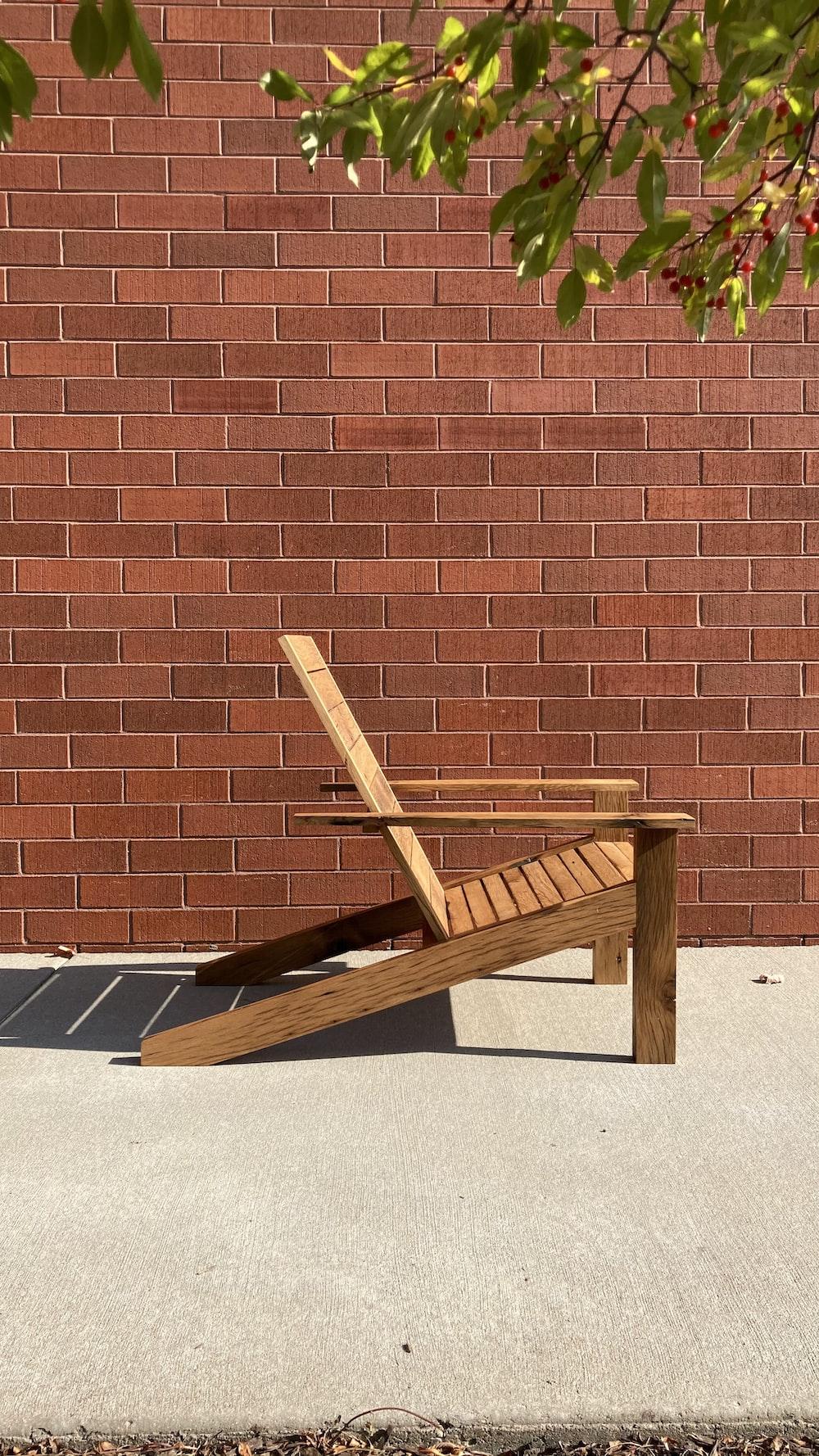 brown wooden folding chair beside brown brick wall