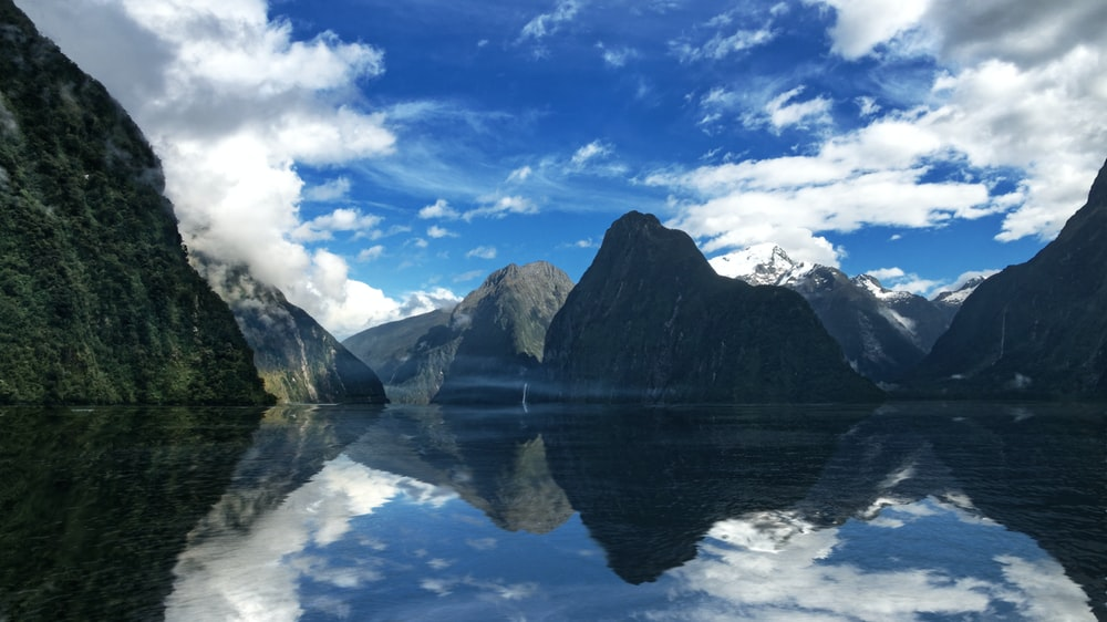 lake near mountain under blue sky and white clouds during daytime
