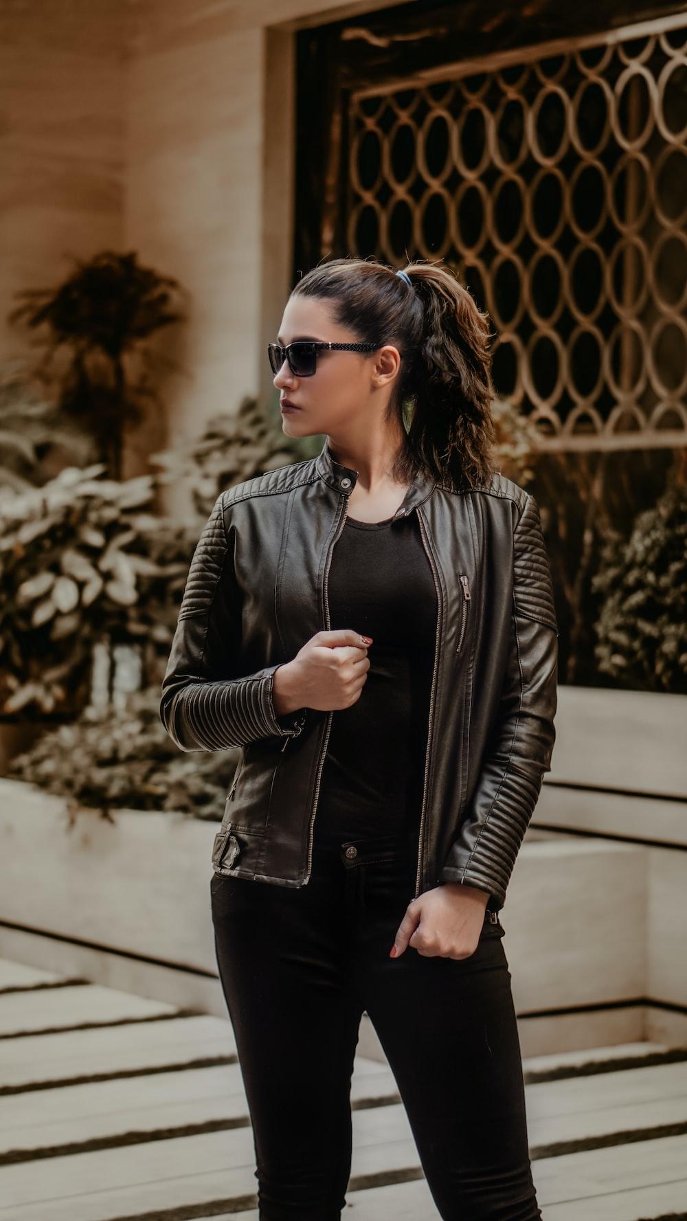 woman in black leather jacket wearing black sunglasses