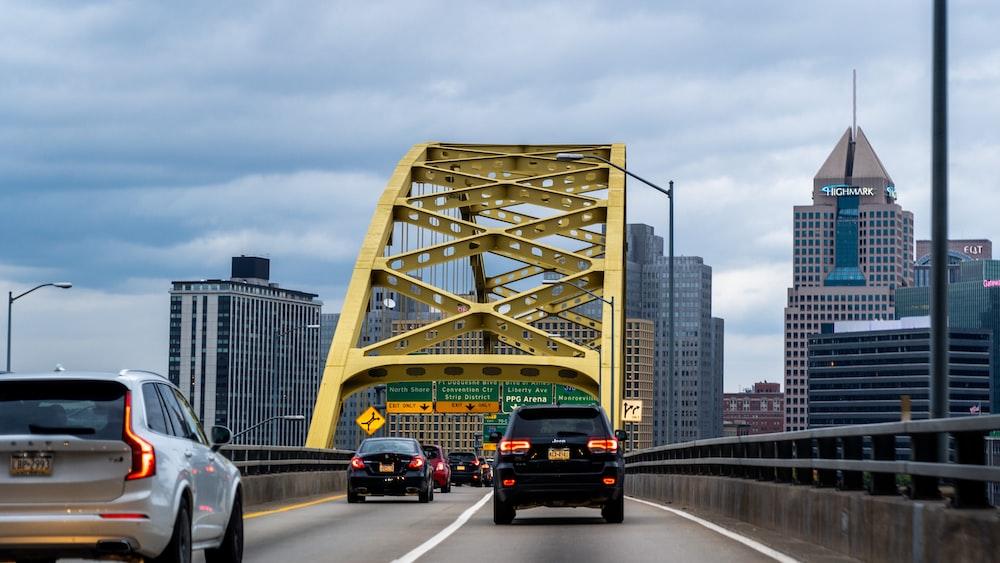 cars on road near bridge during daytime