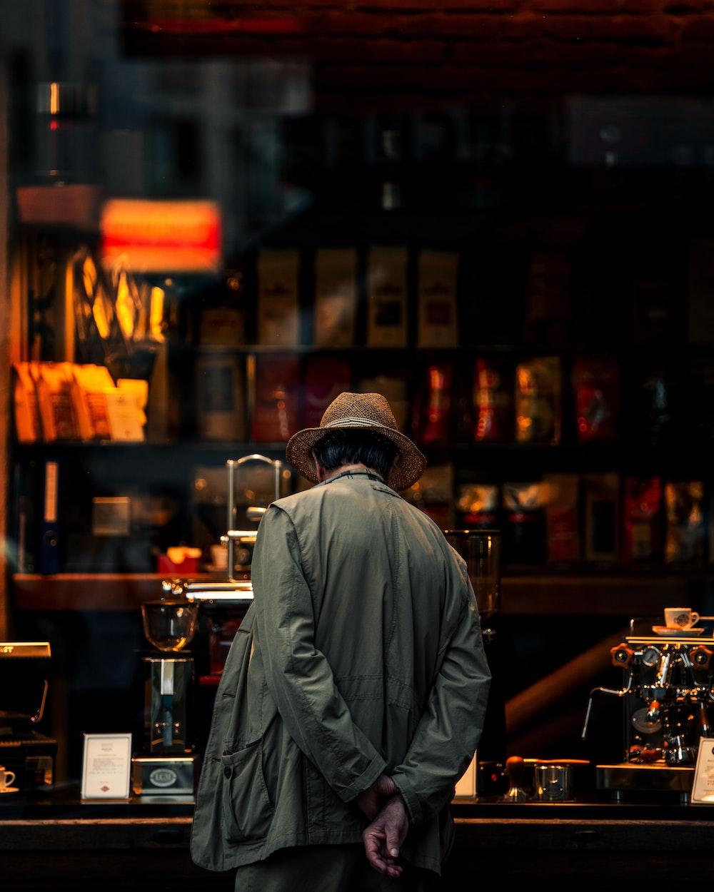 man in gray jacket standing in front of brown wooden shelf