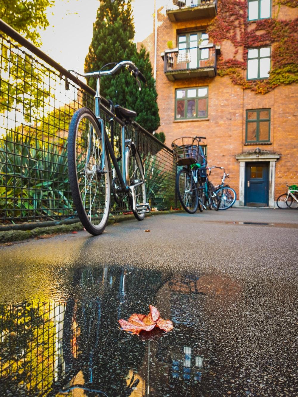 black commuter bike parked beside brown concrete building during daytime