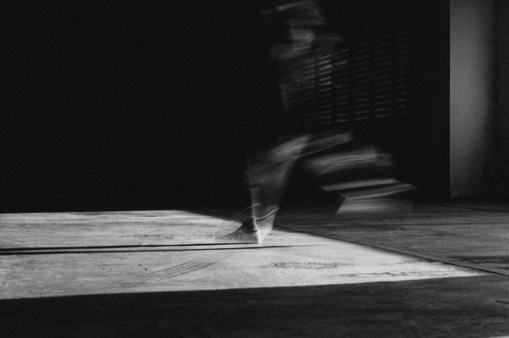 grayscale photo of person standing on wooden floor