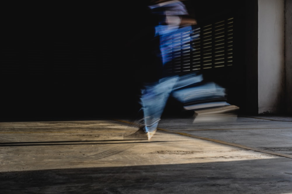 person in black shirt and blue denim jeans walking on brown wooden floor