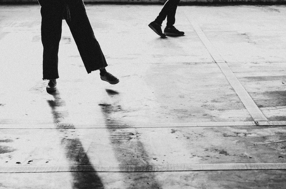 person walking on gray concrete floor