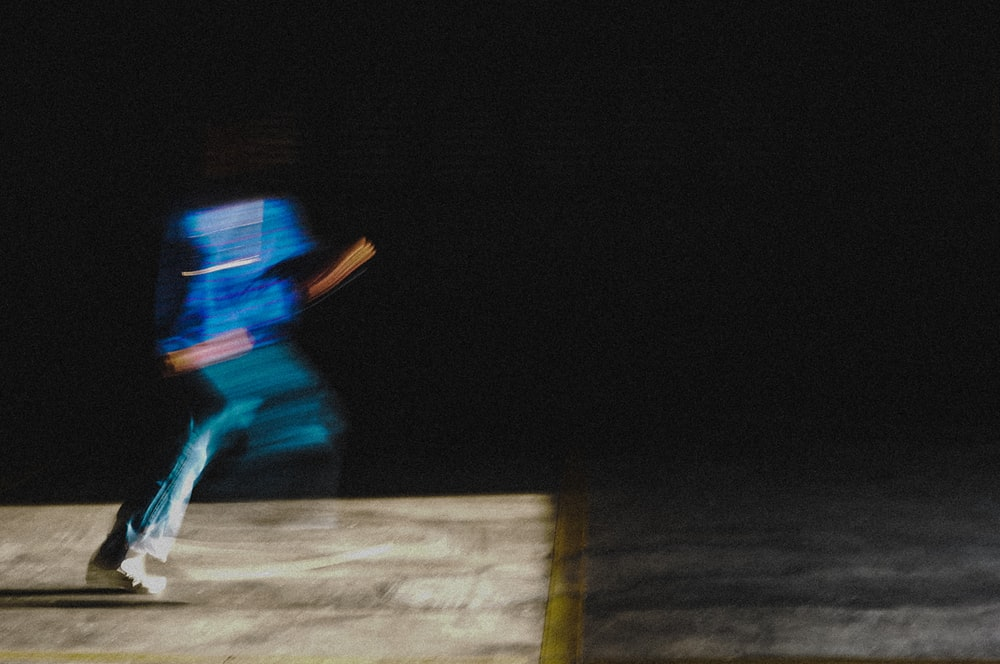 man in blue jacket and blue denim jeans walking on brown wooden plank during nighttime