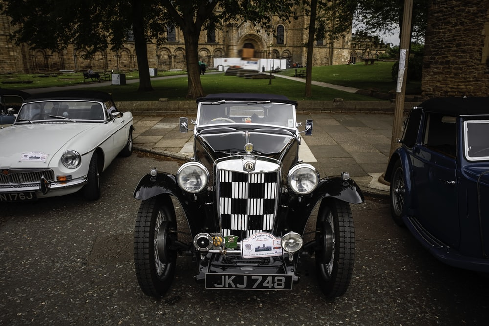 white and black vintage car on green grass field during daytime
