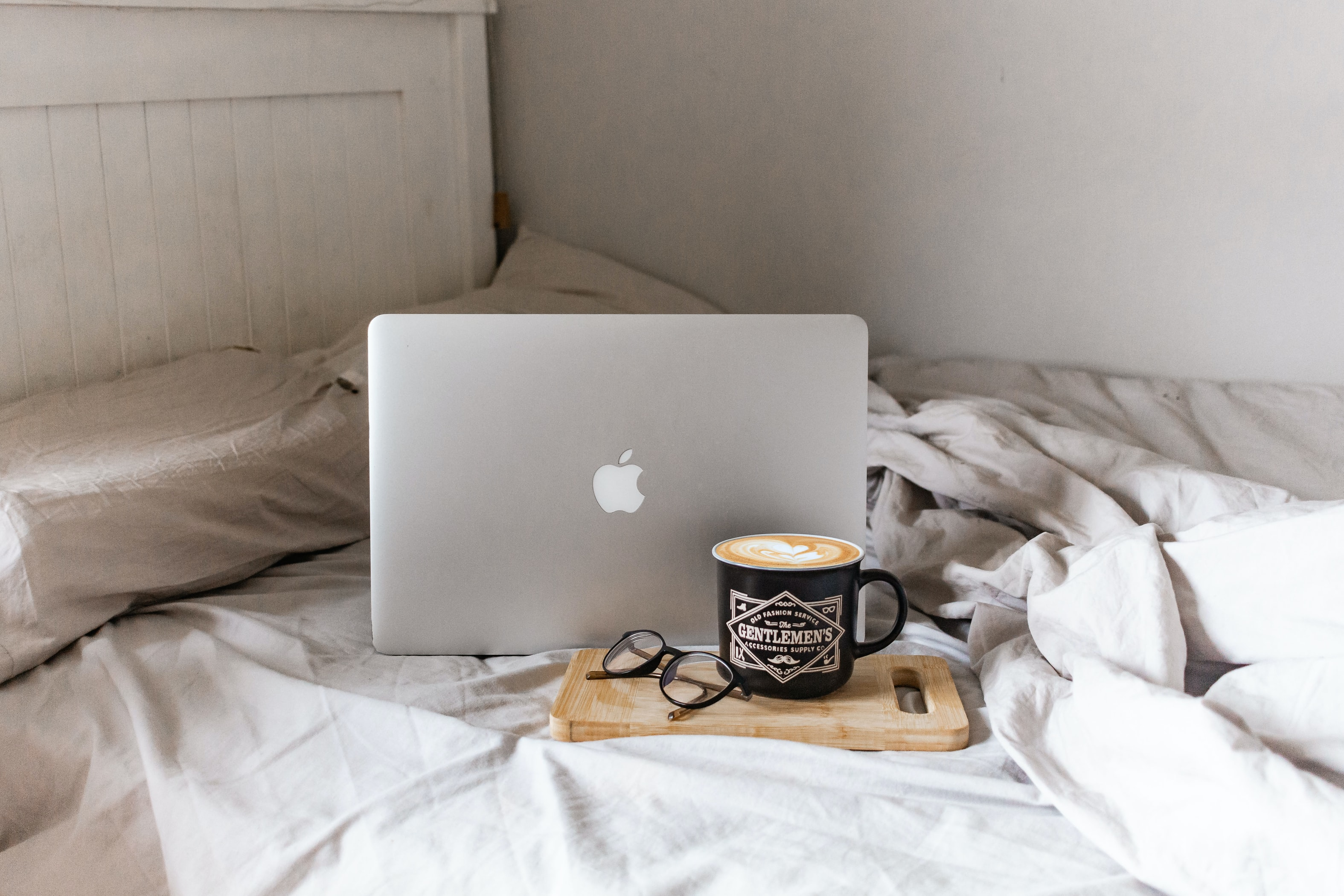 Laptop on a bed next to a coffee.