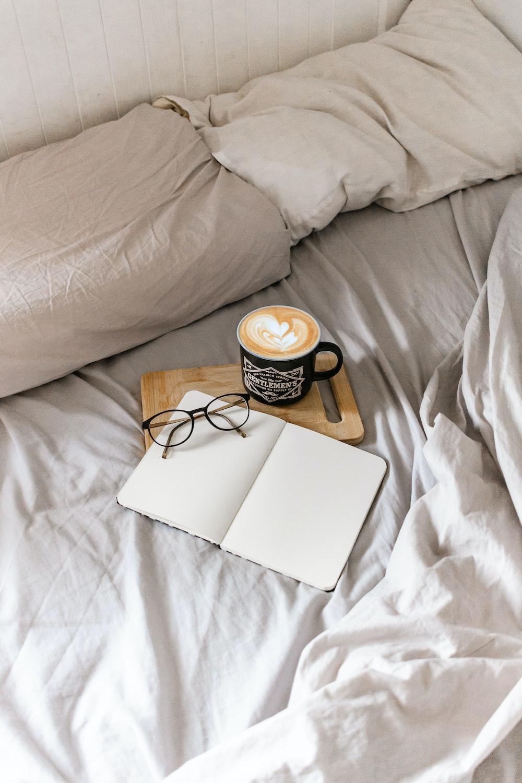white and black ceramic mug on white book