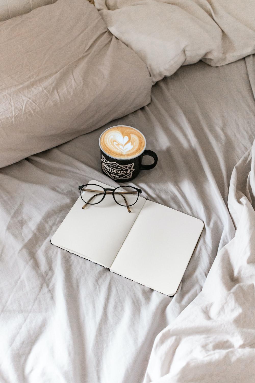 black framed eyeglasses on white book beside black ceramic mug on white bed