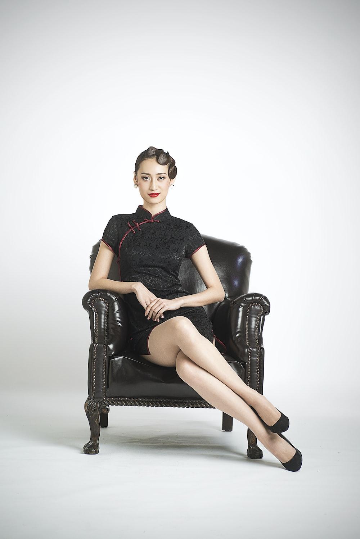 woman in black sleeveless dress sitting on black leather armchair