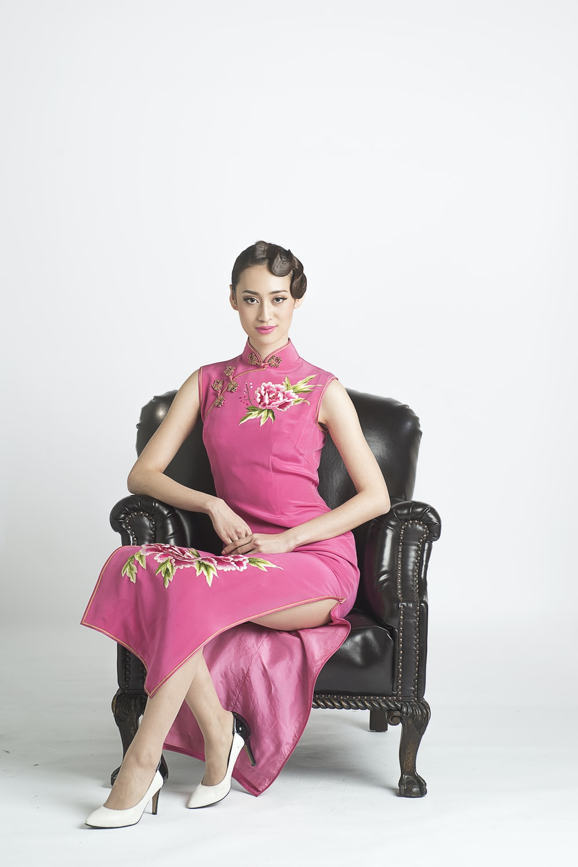 woman in purple sleeveless dress sitting on black leather armchair