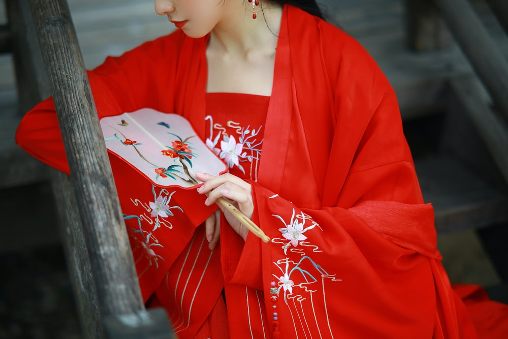 woman in red and white kimono holding white and red floral hand fan