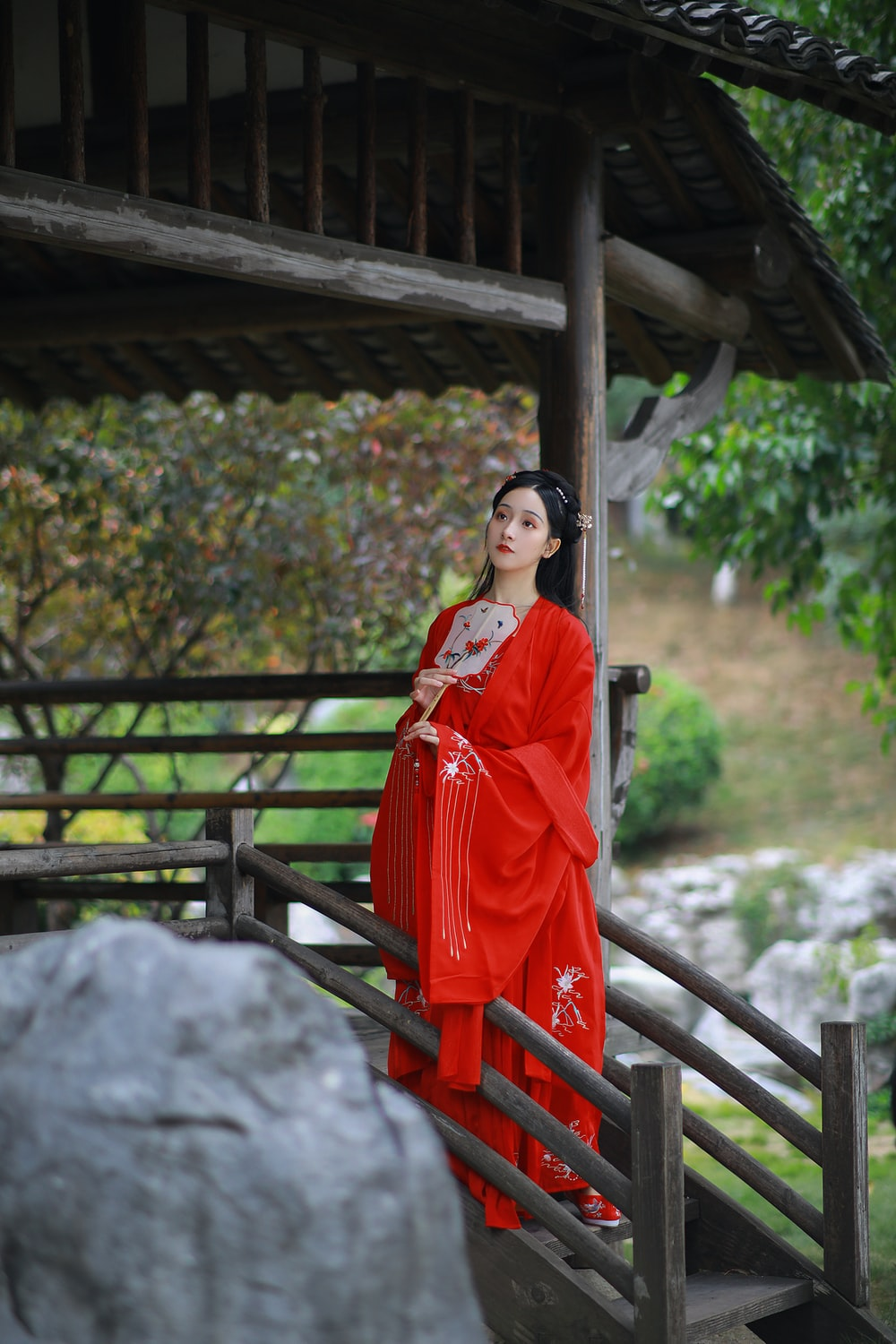 woman in red and white sari standing near brown wooden gazebo during daytime