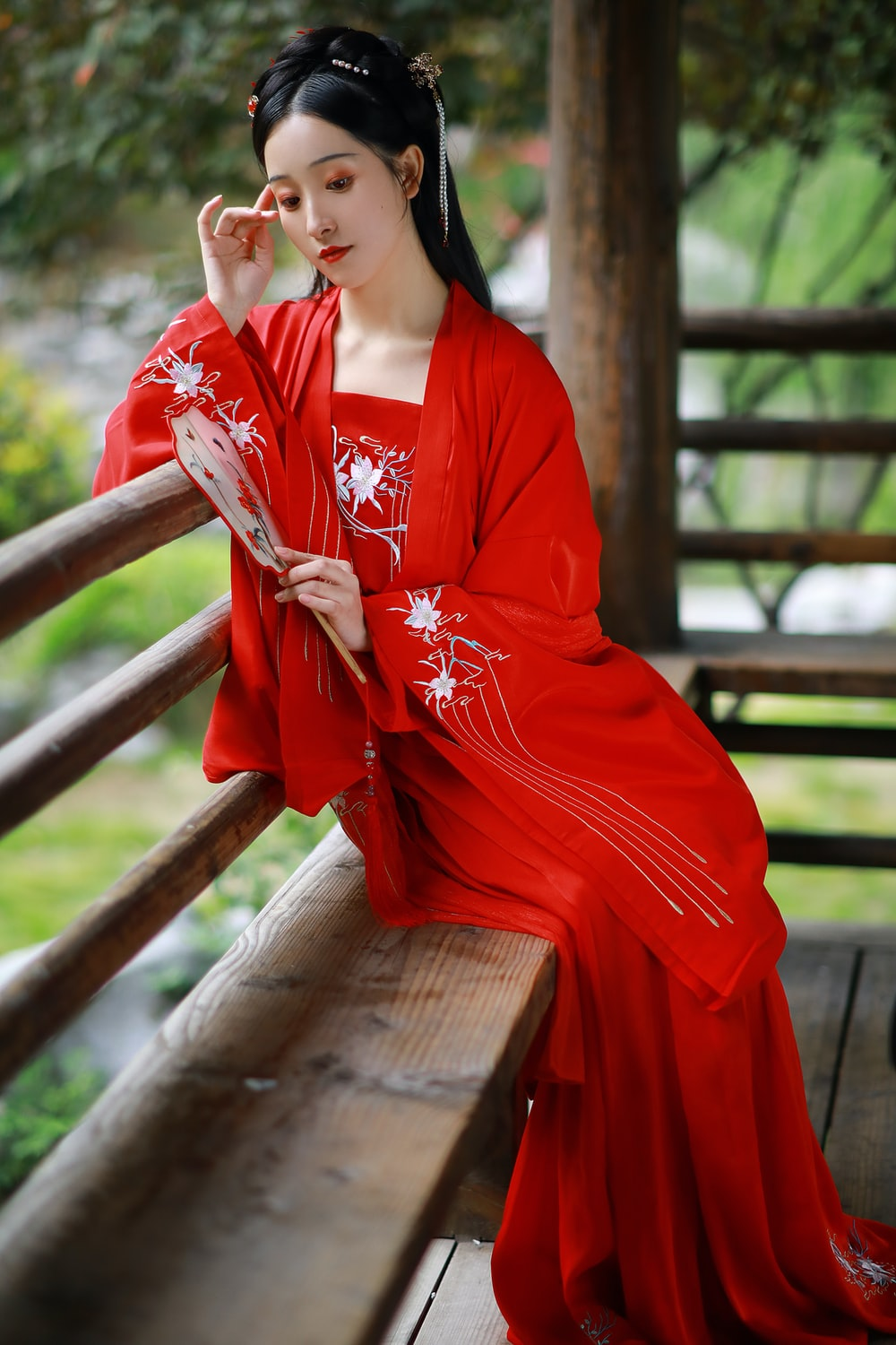 woman in red and white floral kimono sitting on brown wooden bench during daytime