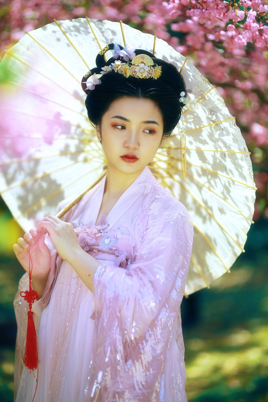 woman in pink kimono holding umbrella