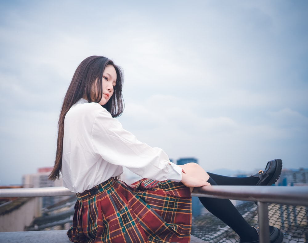 woman in white long sleeve shirt and red and black plaid skirt standing beside railings