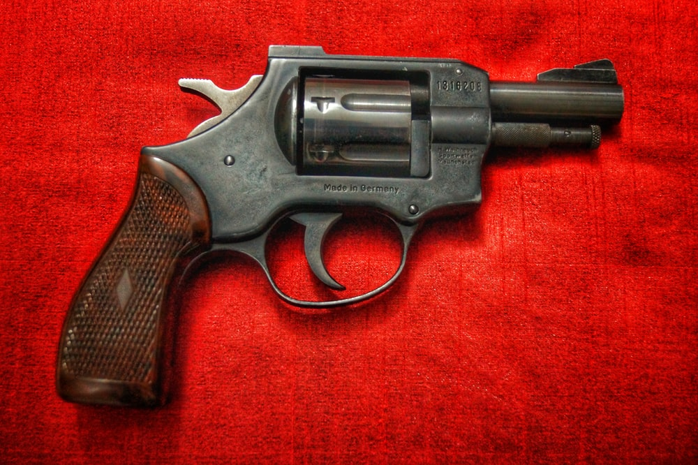 black and silver revolver on red textile