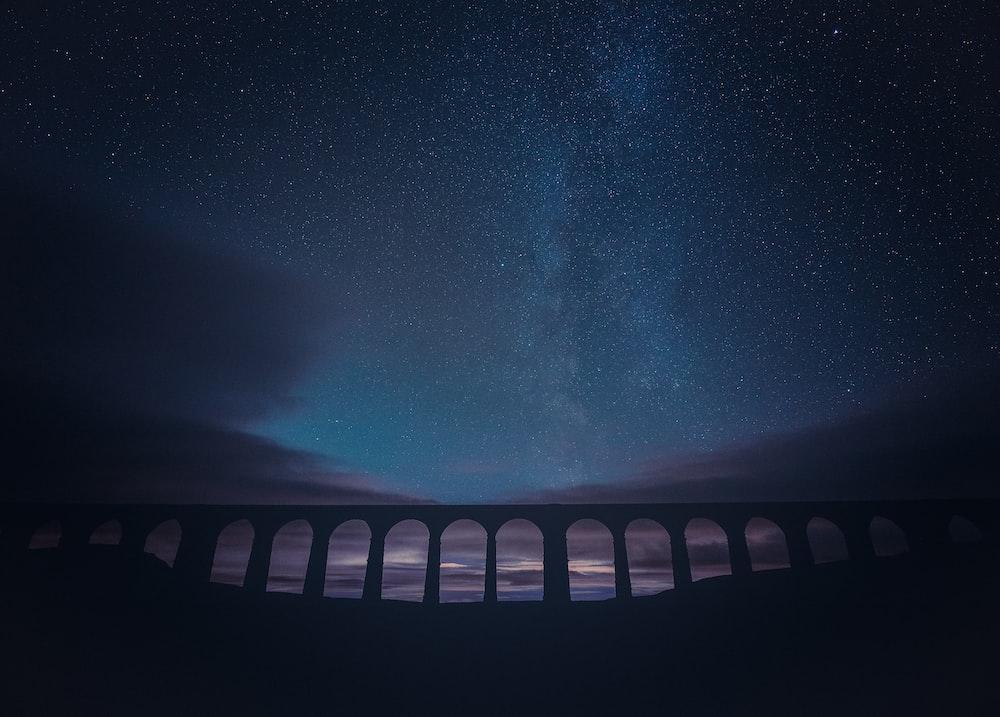 black and white bridge under starry night