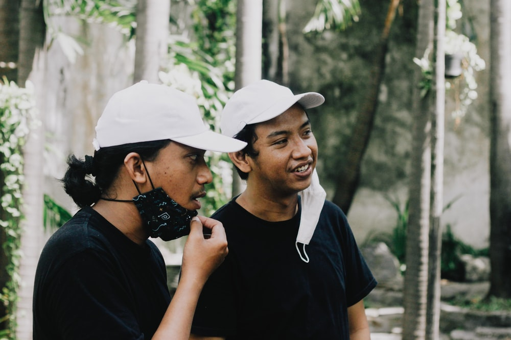 man in black crew neck t-shirt and white cap