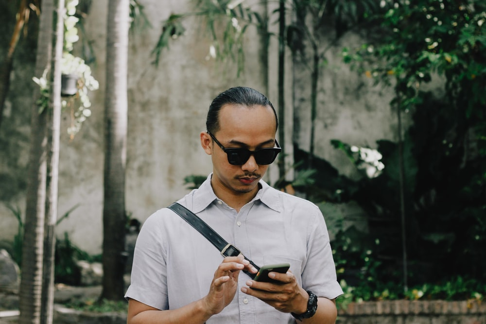 man in white button up shirt wearing black sunglasses holding black smartphone