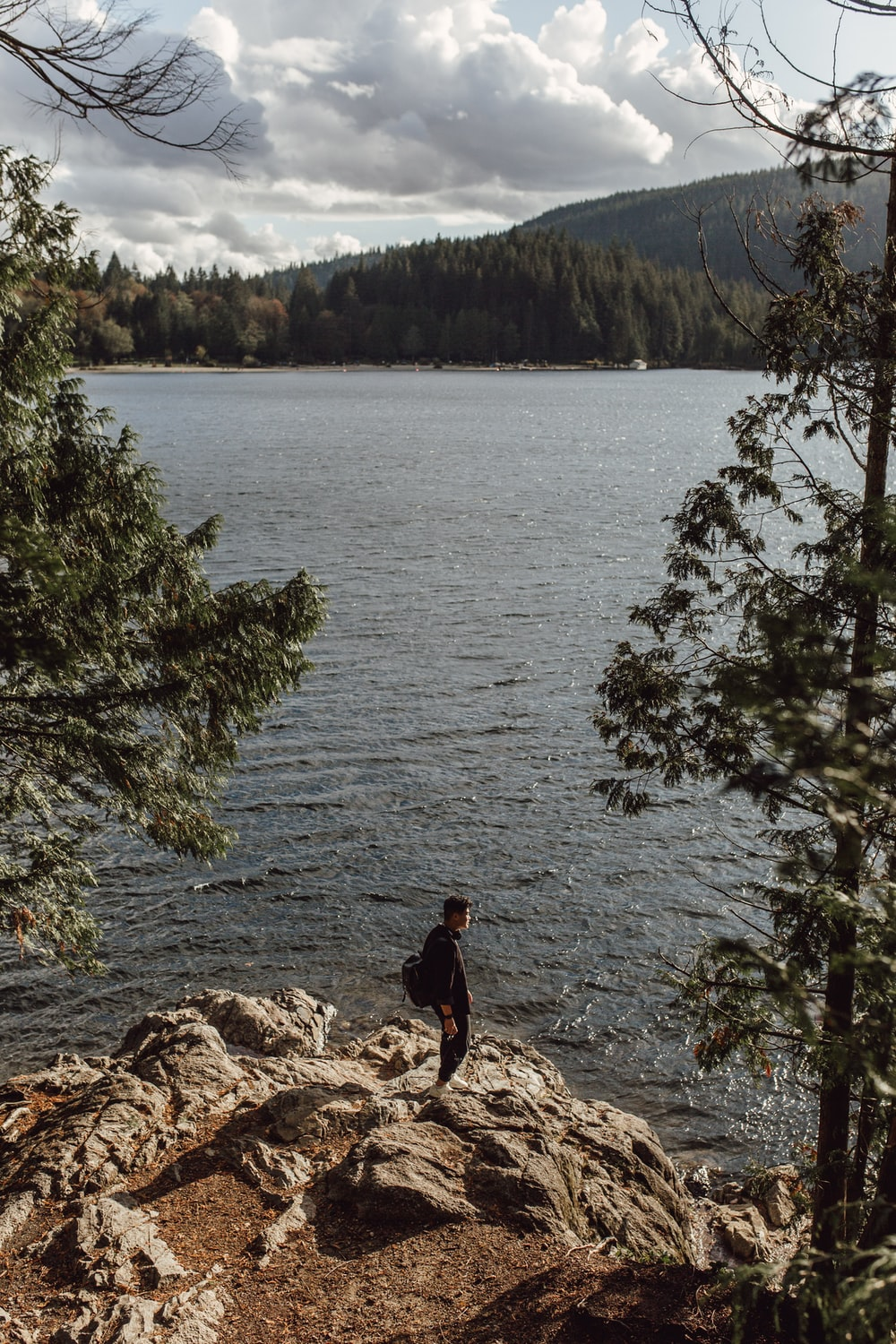 person in black jacket standing on rock near body of water during daytime