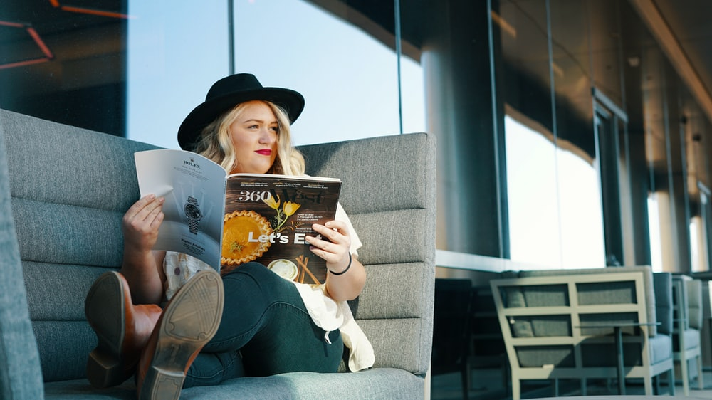 woman in blue denim jeans reading book