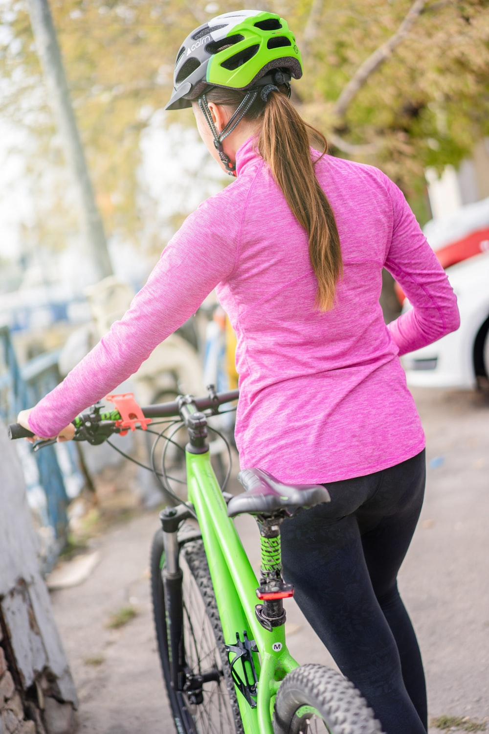 woman in pink long sleeve shirt and black pants riding green bicycle during daytime