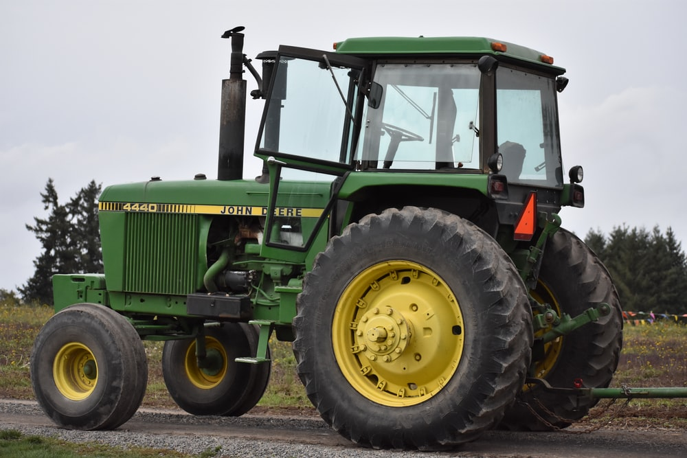 green tractor on brown soil