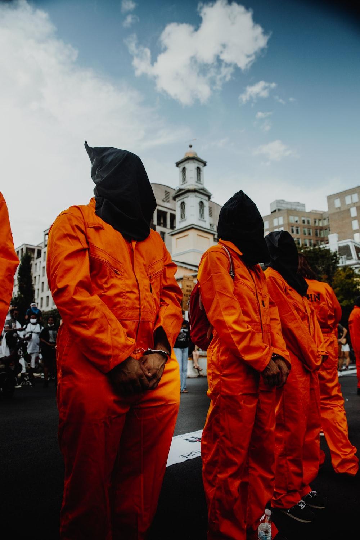 people in orange jacket standing on street during daytime