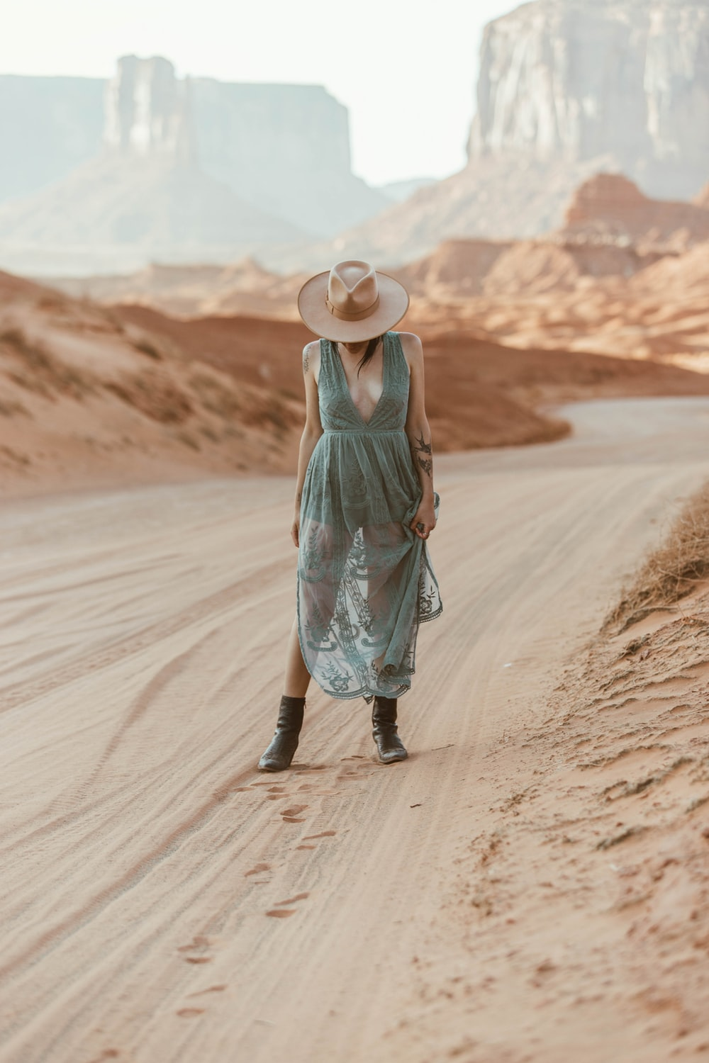 woman in green tank top and blue skirt walking on brown sand during daytime