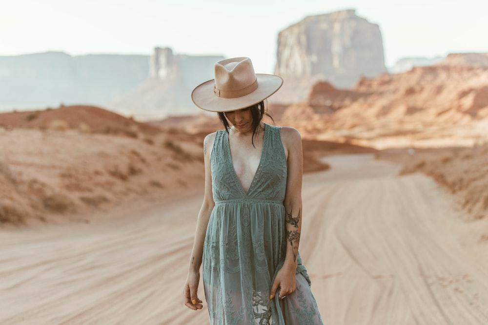 woman in blue sleeveless dress wearing white cowboy hat walking on brown sand during daytime