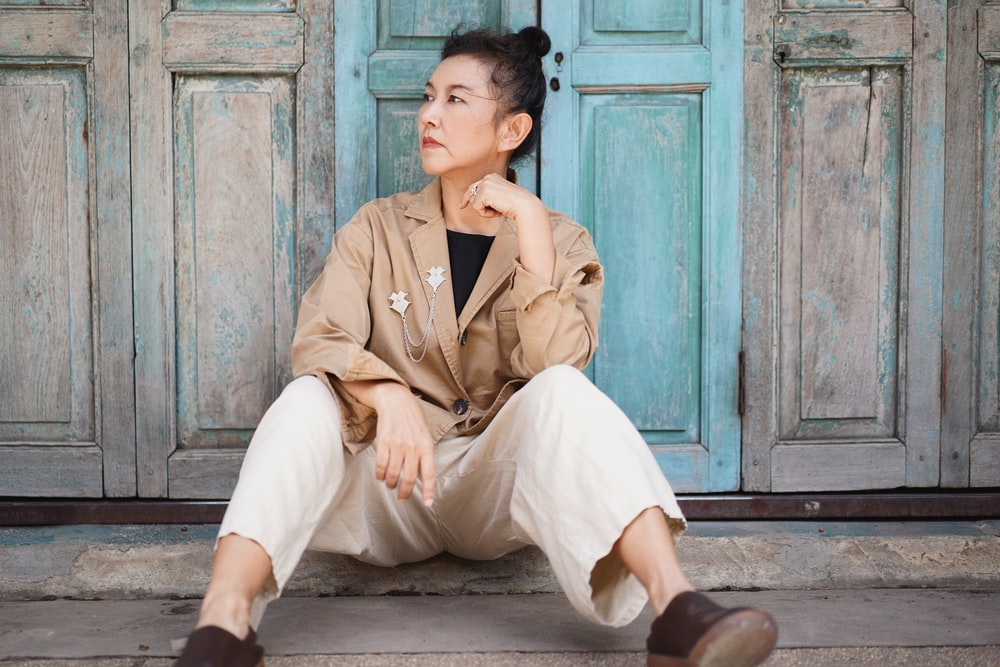 man in brown button up shirt and white pants sitting on brown wooden bench