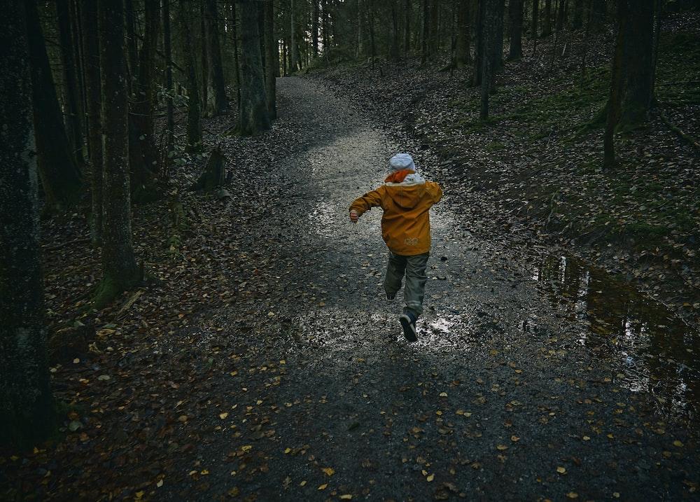 child in brown jacket walking on pathway
