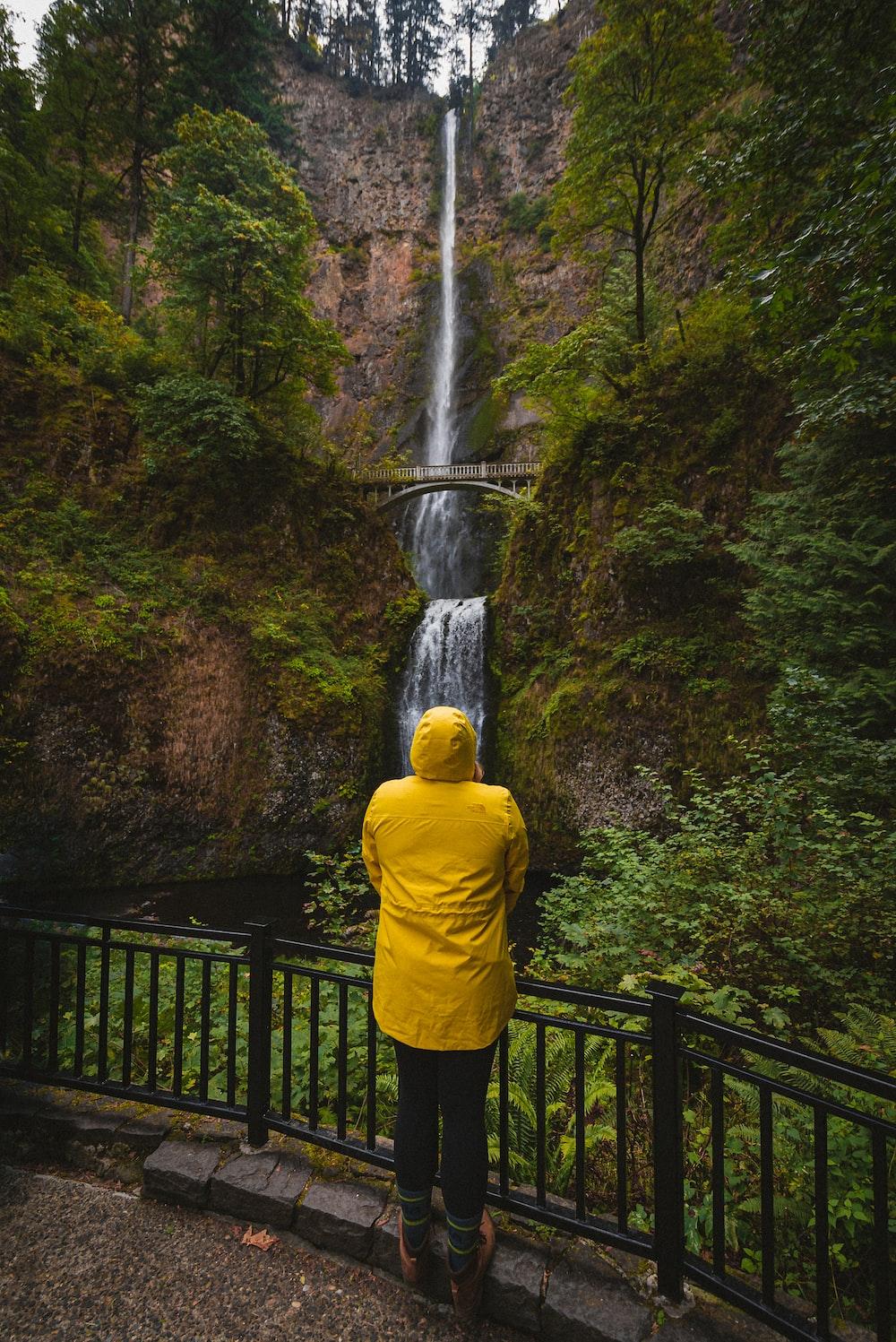 person in yellow hoodie standing on black metal bridge near waterfalls during daytime