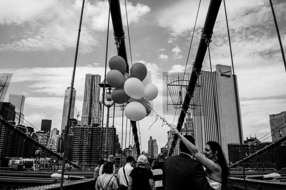 grayscale photo of people walking on street with balloons